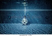 man-sitting-on-the-bottom-of-the-swimming-pool-under-water-fj1b33