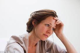 woman with worried look resting head in hand
